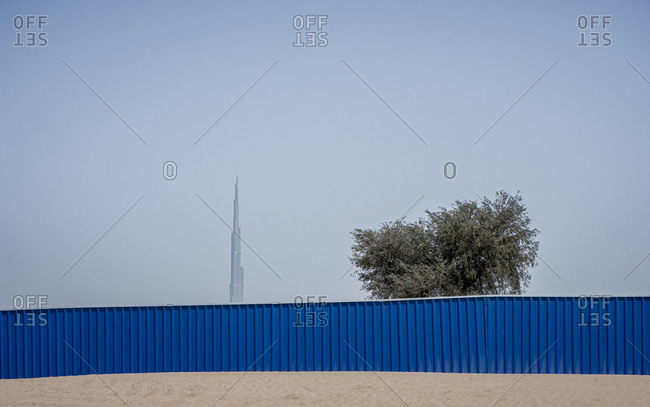 Dubai, United Arab Emirates - April 6, 2018: The desert border with blue wall and a tree with the Burj Khalifa skyscraper in the background