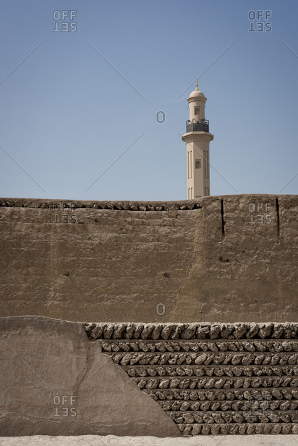 Outer wall of the Al Fahidi Fort with the tower of the Grand mosque in Dubai in the United Arab Emirates