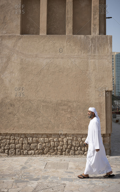 Dubai, United Arab Emirates - April 6, 2018: Man walking in a traditional kandura in the Al Fahidi district in Bur Dubai