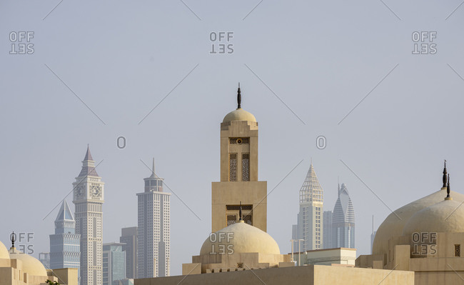Domes of a mosque with skyscrapers in the background in the business district of Dubai, United Arab Emirates