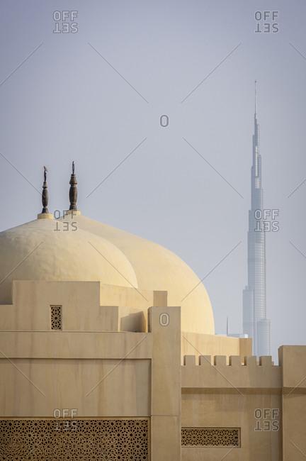 Dubai, United Arab Emirates - April 6, 2018: Domes of a mosque and the Burj Khalifa skyscraper in the distance