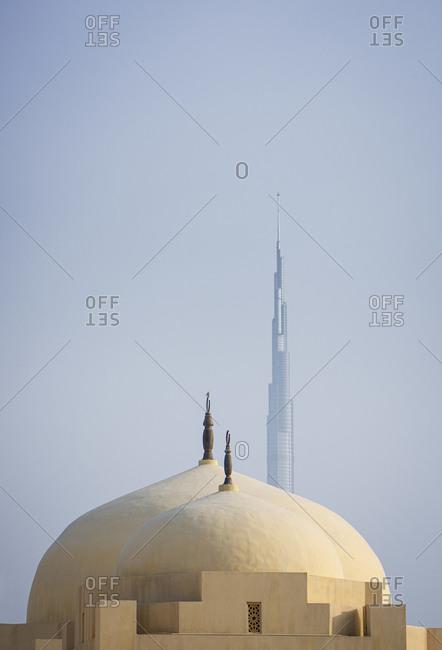 Domes of a mosque and the Burj Khalifa skyscraper in the distance in Dubai, United Arab Emirates