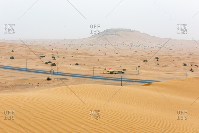 Road and a roadside cafe through the middle of the desert in the United Arab Emirates
