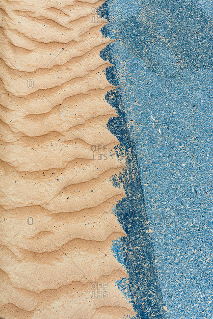 Desert sand and a concrete road meet on the edge of the desert in United Arab Emirates