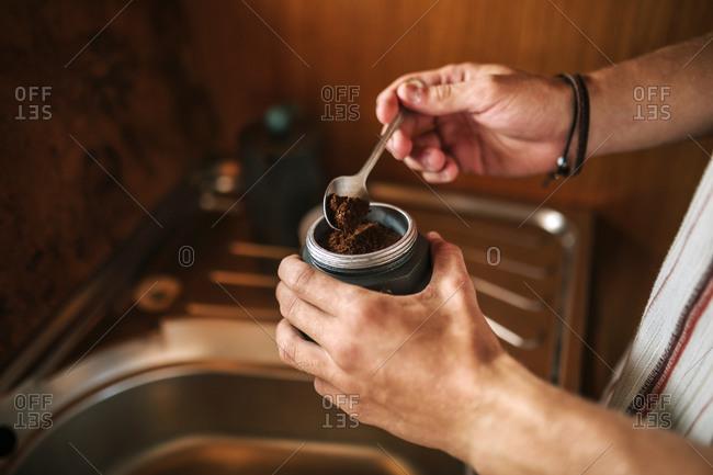 Hands of teenage boy preparing coffee inside a caravan