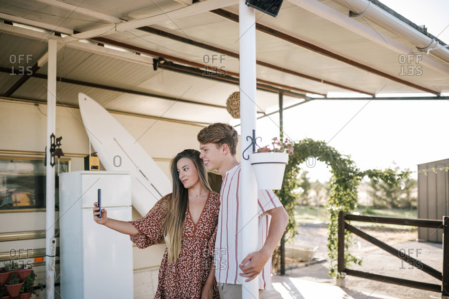 Teenage couple taking a selfie with their mobile phone in front of a caravan