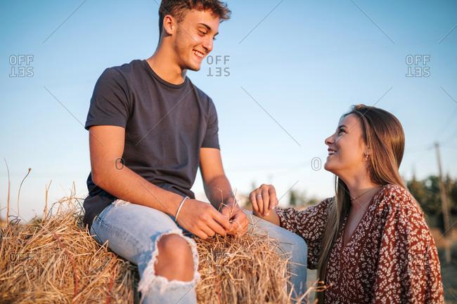 Couple of teenage friends talking in field