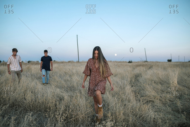 Three young friends walking in the field