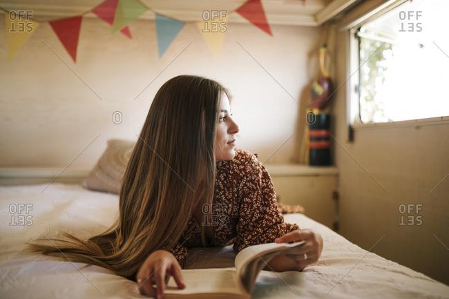 Young woman reading a book inside a caravan