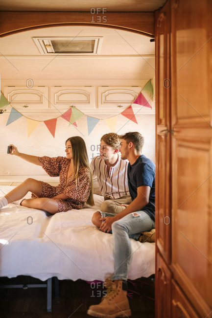 Group of three young friends taking a selfie with mobile phone in a caravan