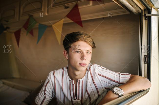 Portrait of young blond boy inside a caravan