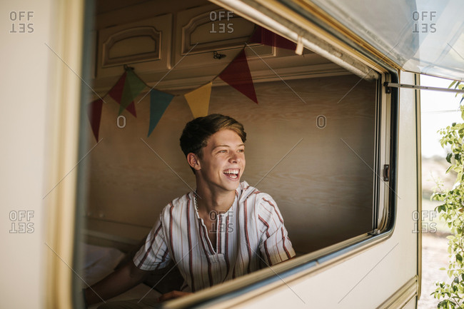 Portrait of young blond man smiling inside a caravan