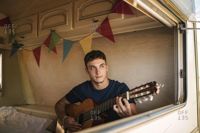 Young man playing guitar inside a caravan