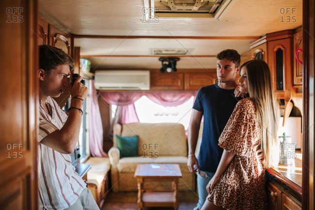 Young man with a camera taking photos of his friends inside a caravan