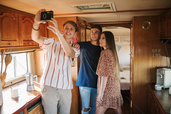 Group of three young friends taking a selfie with a camera in a caravan