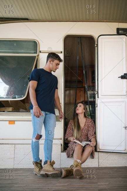 Couple of friends talking at the door of a caravan while young woman holds a book in her hand