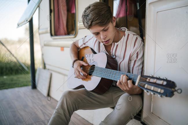 Young teenage man playing guitar sitting in the doorway of a caravan