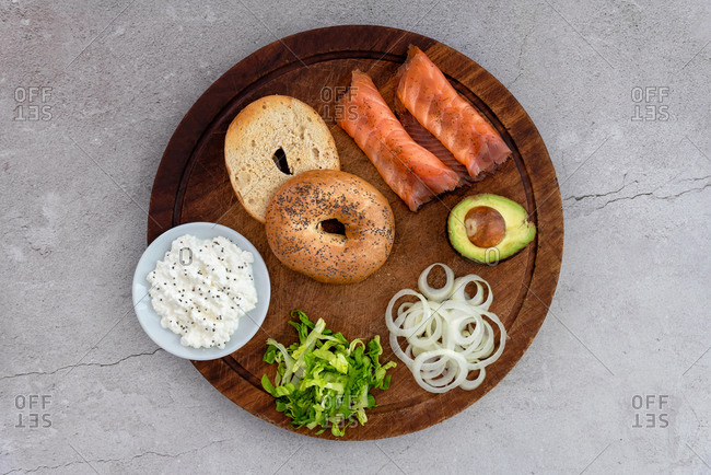 Salmon bagel with ingredients arranged on a wooden table