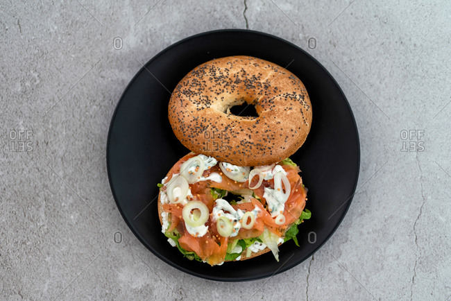 Salmon bagel with cream cheese, fresh herbs and veggies on a marble counter