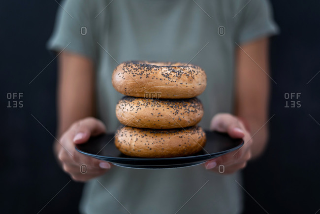 A women's hands holding a plate full of bagels on a black background