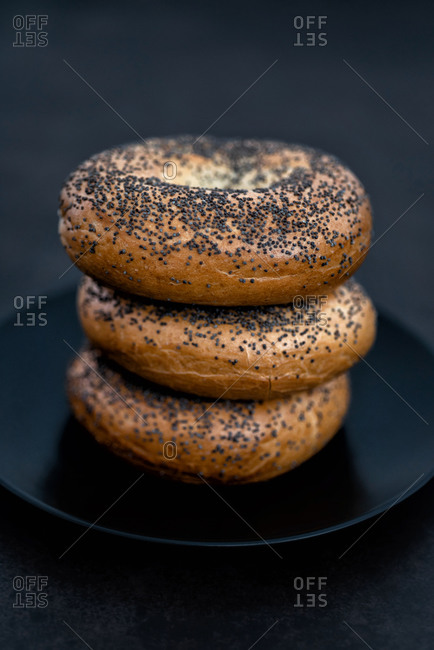 Black plate full of bagels on a black background