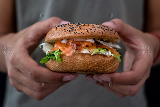 Woman holding a lox bagel with cream cheese and veggies