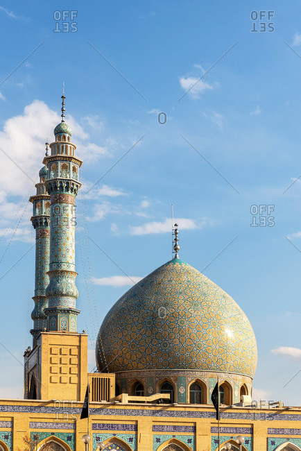 Exterior view of an oriental Mosque with decorative tiles and a dome in Qom, Iran