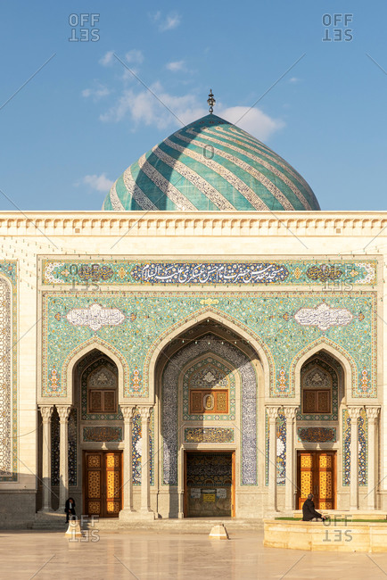 February 28, 2018: People sitting in front of a mosque with ornamental tiles on the wall in Qom, Iran.