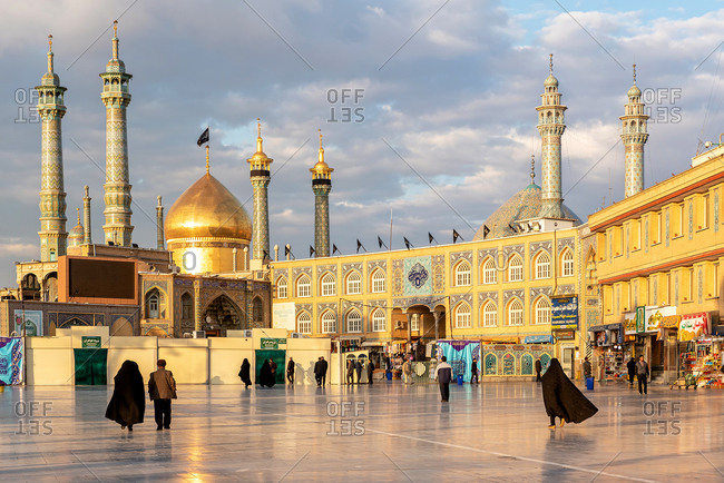 March 1, 2018: People walking in front of a mosque with ornamental tiles on the wall in Qom, Iran.