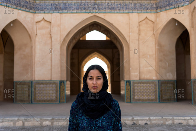 Ethnic woman in traditional clothes standing at Middle Eastern building with arch in Khasan, Iran.