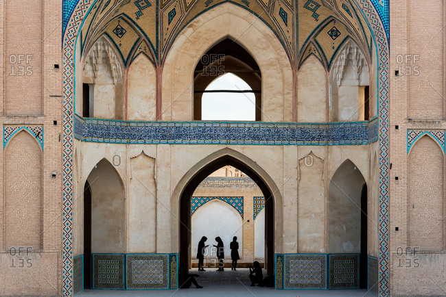 People in front of a mosque with ornamental tiles on the wall in Khasan, Iran.