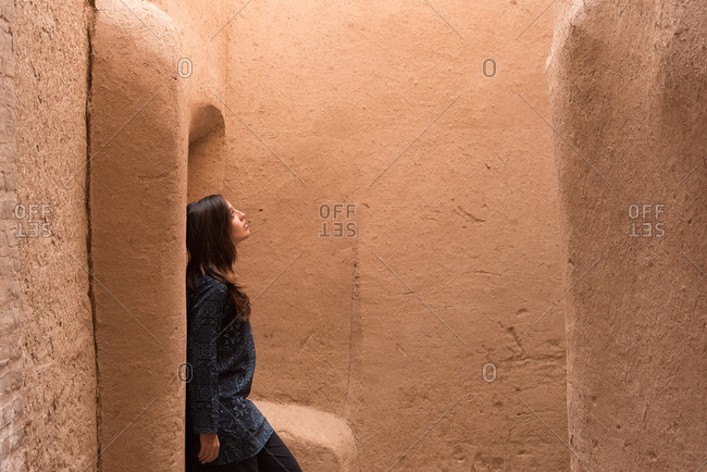 Side view of adult woman leaning on sandy yellow wall in narrow street in Yazd, Iran