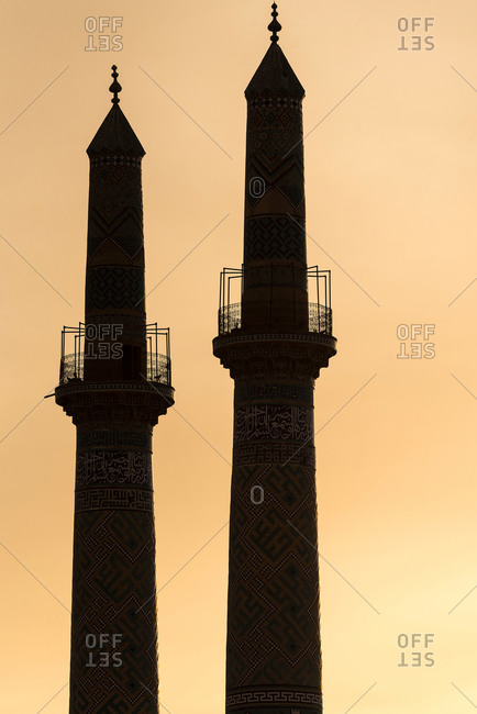 Silhouette of two minarets in sunset lights in Yazd, Iran.