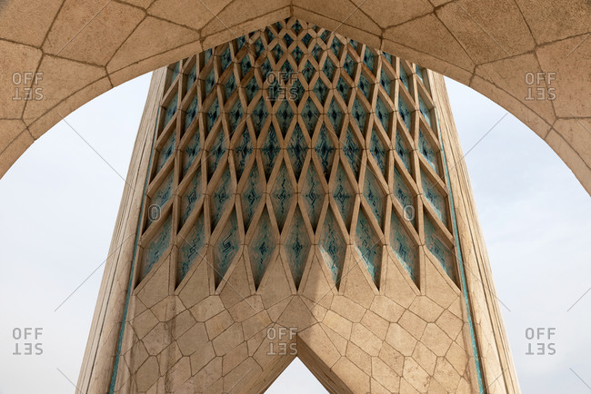 Detail of the modern Azadi tower on a gray cloudy day in Tehran, Iran