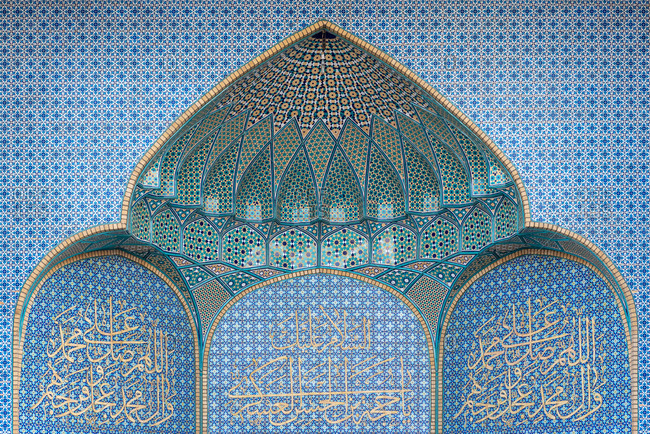 February 28, 2018: Exterior of mosque facade with white columns and amazing ornamental tiles decorating a wall in Qom, Iran.