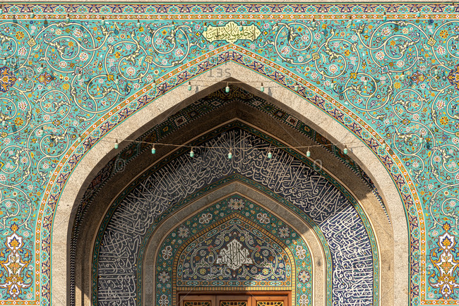 February 28, 2018: Exterior of mosque facade with white columns and amazing ornamental tiles decorating wall, Iran.