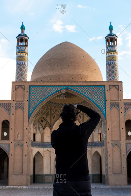 Back view of photographer man taking shots of mosque in Khasan, Iran.