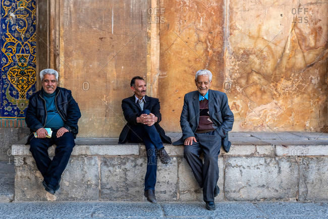 March 3, 2018: Three old Iranian men sitting in front of a mosque in Isfahan, Iran