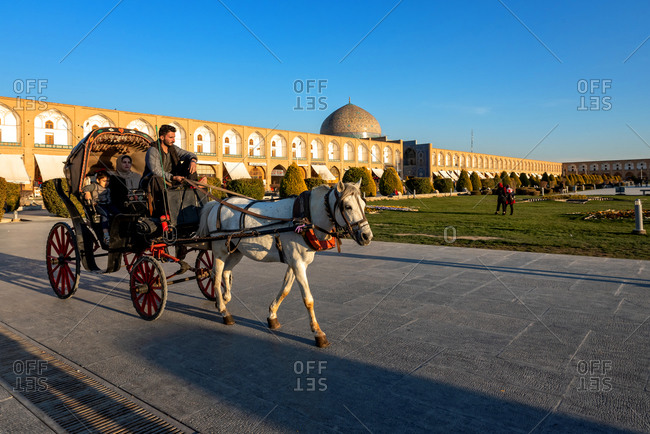 March 3, 2018: Horse and cart carrying Iranian tourists around Imam Square in Isfahan, Iran