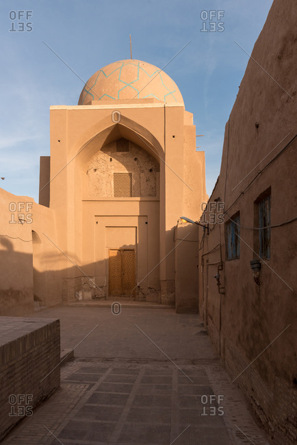 View of traditional Middle Eastern mosque with cupola on sunny street in Yazd, Iran.