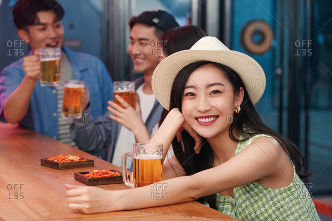 Young women drinking with friends in a bar