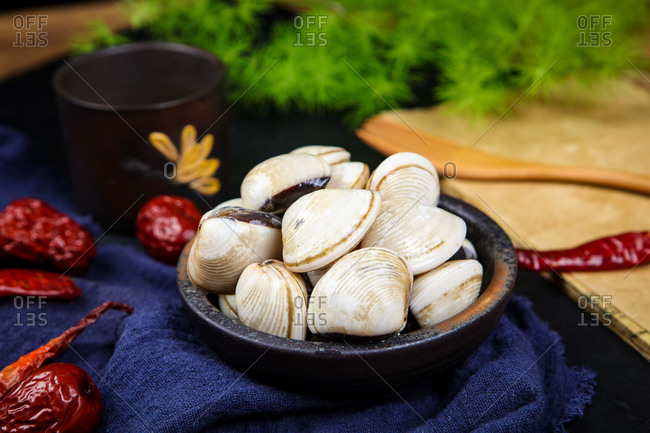 Bowl of clams surrounded by cayenne peppers