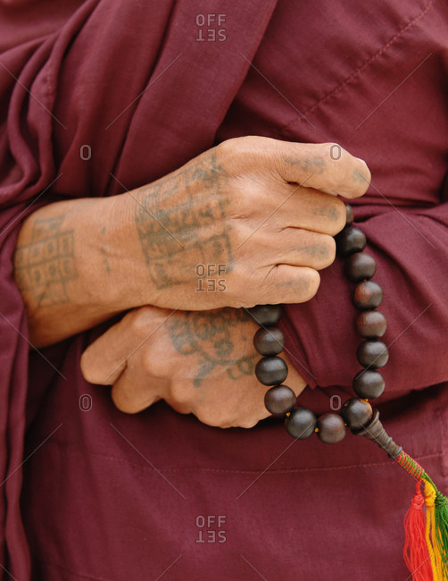 December 11, 2013: Close up of Buddhist monk holding holy beads, Burma