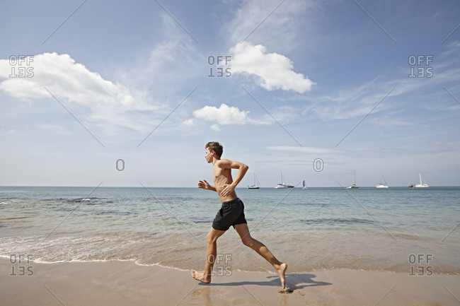 Young man running along seashore, Koh Lipe, Thailand
