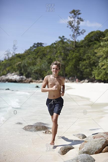 Young man running along beach, Koh Lipe, Thailand
