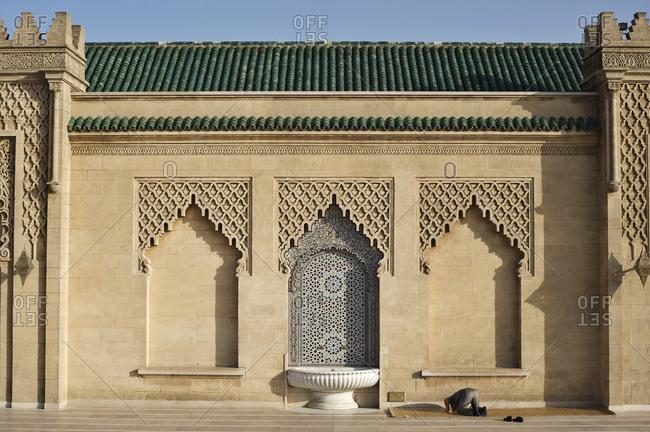 Man praying outside building in Rabat, Rabat-Sale.-Zemmour-Zaer region, Morocco