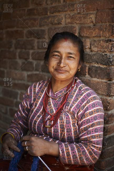 February 28, 2013: Portrait of street trader with knitting, Thamel, Kathmandu, Nepal