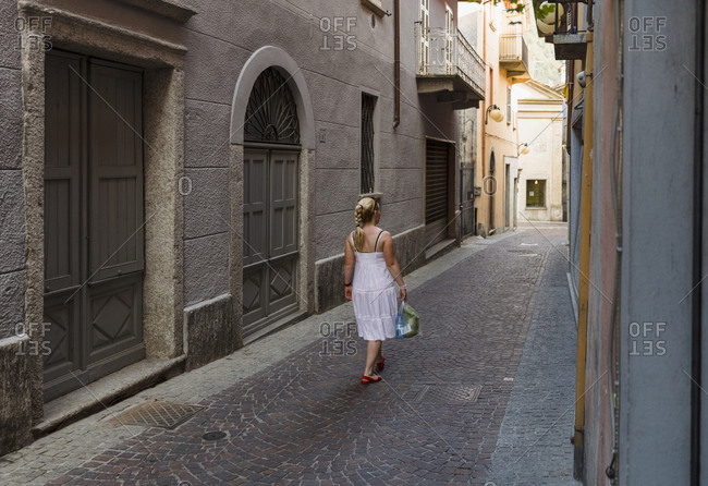 Mid adult female tourist strolling, Omegna, Italy