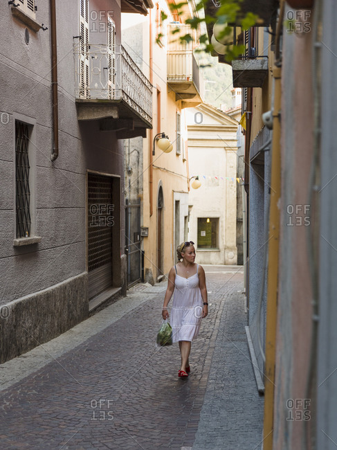 Mid adult female tourist strolling in Omegna town, Italy