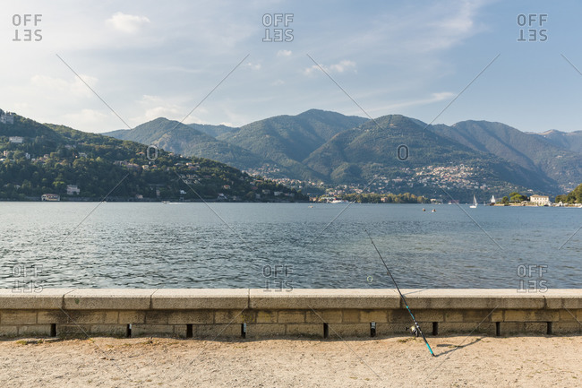 Fishing rod resting on harbor wall, Como, Italy